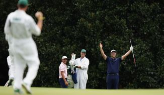 Rickie Fowler, left, watches as Jon Rahm, of Spain, celebrates chipping into the hole on eat 16th green during a practice round for the Masters golf tournament Tuesday, Nov. 10, 2020, in Augusta, Ga. (AP Photo/Matt Slocum)