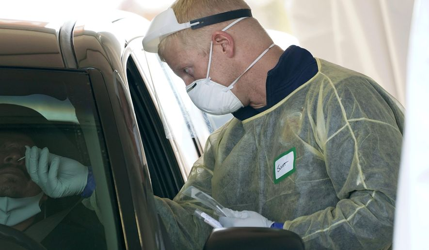 In this Oct. 28, 2020, file photo, a worker wearing gloves, a face shield, a mask, and other PPE administers a COVID-19 test at a King County coronavirus testing site in Auburn, Wash., south of Seattle. The latest surge in U.S. coronavirus cases appears to be larger and more widespread than the two previous ones, and it is all but certain to get worse. But experts say there are also reasons to think the nation is better able to deal with the virus than before, with the availability of better treatments, wider testing and perhaps greater political will. (AP Photo/Ted S. Warren, File)