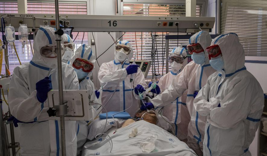 In this Friday, Oct. 9, 2020, filer, a patient infected with COVID-19 is treated in one of the intensive care units (ICU) at the Severo Ochoa hospital in Leganes, outskirts of Madrid, Spain. Intensive care space is dwindling across Europe as beds fill again with coronavirus patients, this time in places that had been spared the virus peak from last spring. (AP Photo/Bernat Armangue, File)