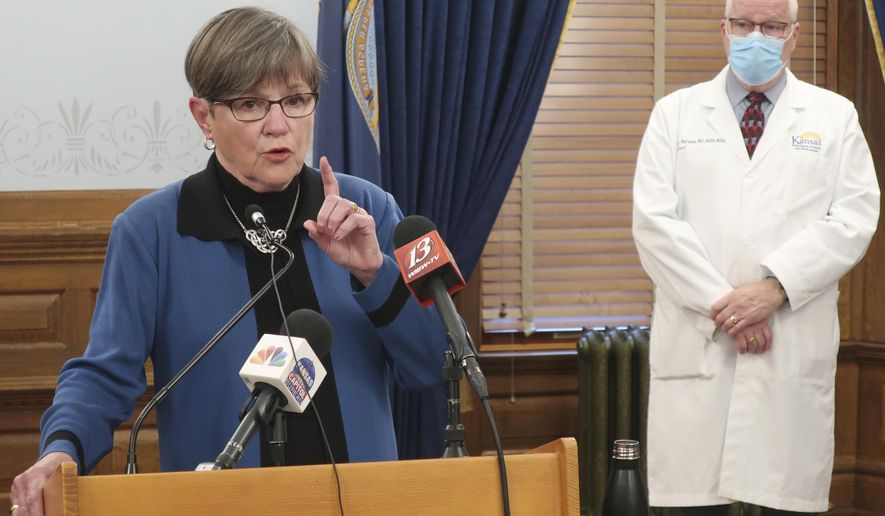 Kansas Gov. Laura Kelly discusses the coronavirus pandemic as her health secretary, Dr. Lee Norman, watches behind her at a news conference, Tuesday, Nov. 10, 2020, at the Statehouse in Topeka, Kan. Kelly says the state's unified strategy for more aggressive testing won't work to curb the spread of the virus if people don't wear face masks and socially distance. (AP Photo/John Hanna)