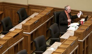 FILE - In this May 15, 2020 file photo, Rep. Roy Edwards, R-Gillette, reaches for some papers while listening to legislators speak during a special legislative session inside the Capitol in downtown Cheyenne, Wyo.  Edwards, 66, who was running unopposed for a fourth two-year term died Monday, Nov. 2, 2020, of an undisclosed illness.  (Michael Cummo/The Wyoming Tribune Eagle via AP, File)