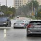 A driver navigates around vehicles stalled in Sarasota, Florida, on Wednesday as Eta passes to the west.