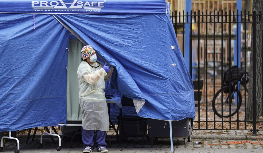 Medical works operate a testing tent at a COVID-19 mobile testing site, Wednesday, Nov. 11, 2020, in the Brooklyn borough of New York. Restaurants, bars and gyms will have to close at 10 p.m. across New York state in the latest effort to curb the spread of the coronavirus, Gov. Andrew Cuomo announced Wednesday. Cuomo said the new restrictions, which go into effect Friday, are necessary because new coronavirus infections have been traced to those types of activities. (AP Photo/John Minchillo)