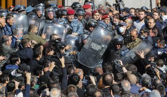 People argue with police during a protest against an agreement to halt fighting over the Nagorno-Karabakh region, in Freedom Square in Yerevan, Armenia, Wednesday, Nov. 11, 2020. Thousands of people flooded the streets of Yerevan once again on Wednesday, protesting an agreement between Armenia and Azerbaijan to halt the fighting over Nagorno-Karabakh, which calls for deployment of nearly 2,000 Russian peacekeepers and territorial concessions. Protesters clashed with police, and scores have been detained. (AP Photo/Dmitri Lovetsky)