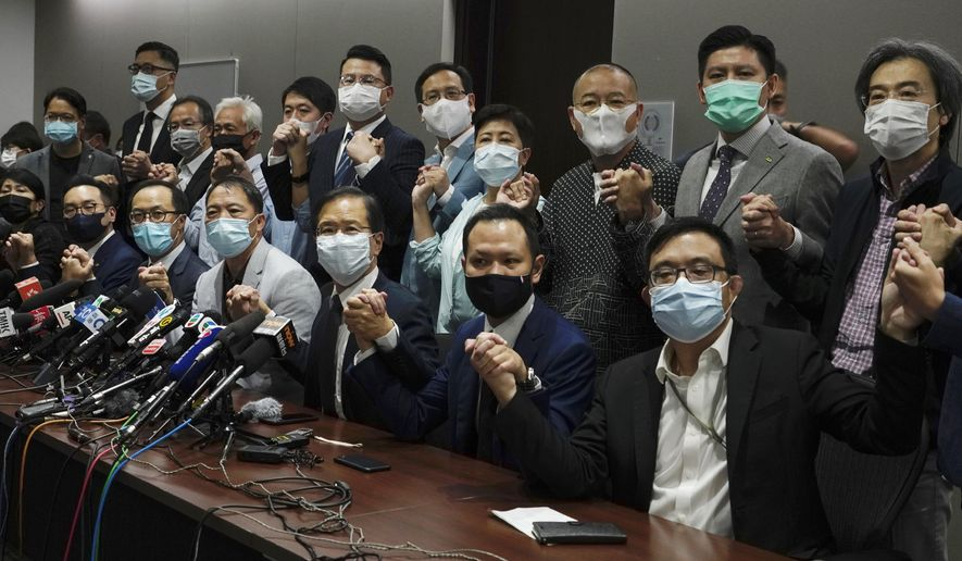 Hong Kong's pro-democracy legislators pose for a photo before a press conference at Legislative Council in Hong Kong, Wednesday, Nov. 11, 2020. Hong Kong's pro-democracy lawmakers announced that they are resigning en masse following a move by the city's government to disqualify four pro-democracy legislators. (AP Photo/Vincent Yu)