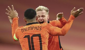 Netherlands' Donny van de Beek, rear, celebrates with Netherlands' Memphis Depay after he scored his side's first goal during the international friendly soccer match between The Netherlands and Spain at the Johan Cruyff ArenA in Amsterdam, Netherlands, Wednesday, Nov. 11, 2020. (Dean Mouhtaropoulos/Pool via AP)