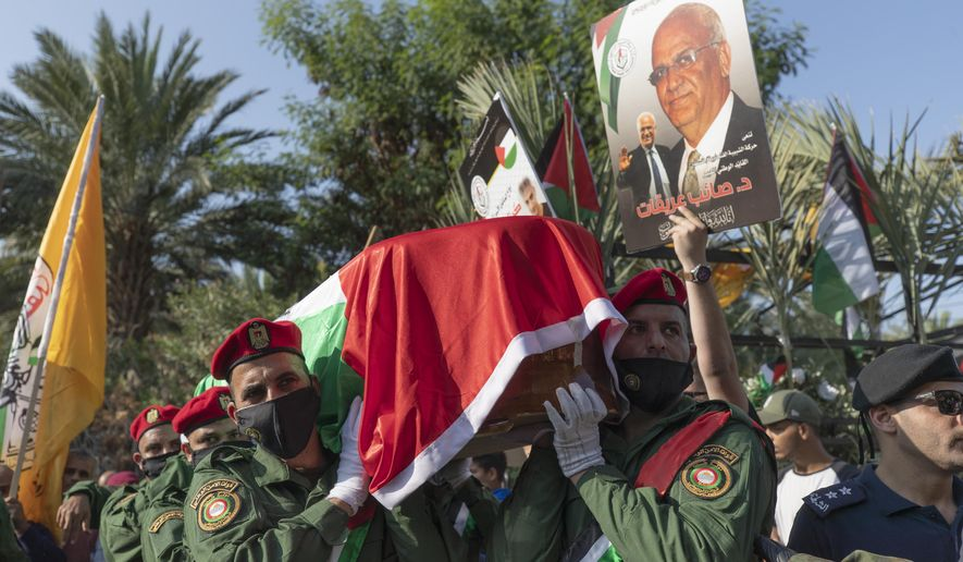 A Palestinian honor guard carries the body of Saeb Erekat into the cemetery during his funeral in the West Bank town of Jericho, Wednesday, Nov. 11, 2020. Erekat, a veteran peace negotiator and prominent international spokesman for the Palestinians for more than three decades, died on Tuesday, weeks after being infected by the coronavirus. He was 65. (AP Photo/Nasser Nasser)