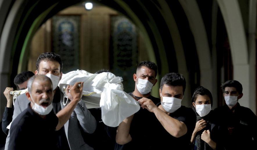 Mourners carry the body of a person who died from COVID-19 at the Behesht-e-Zahra cemetery on the outskirts of Tehran, Iran, Sunday, Nov. 1, 2020. The cemetery is struggling to keep up with the coronavirus pandemic ravaging Iran, with double the usual number of bodies arriving each day and grave diggers excavating thousands of new plots. (AP Photo/Ebrahim Noroozi)