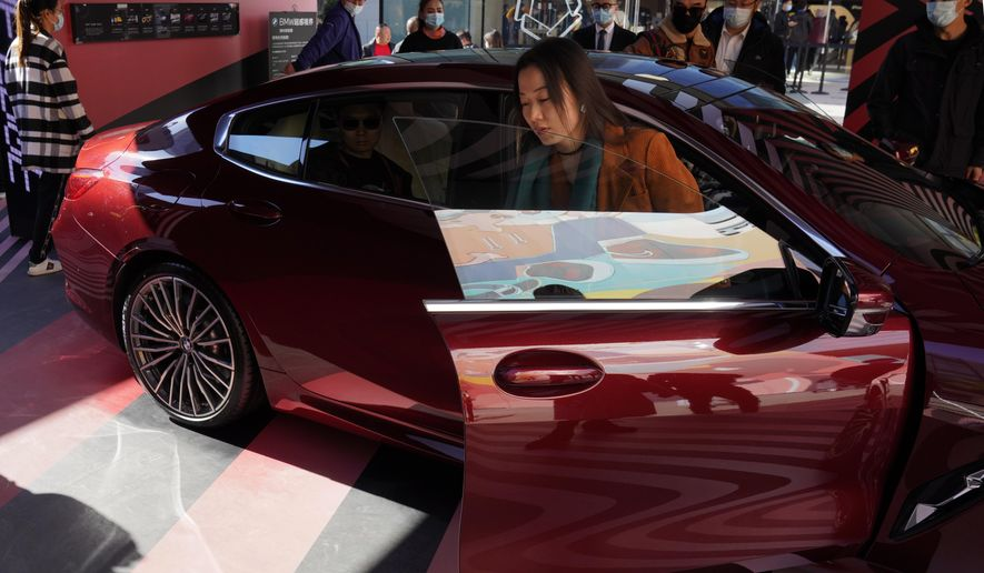 A woman exits a car on display during a promotion held in a popular shopping district in Beijing on Sunday, Nov. 8, 2020. China's sales of vehicles including trucks and buses rose 12.5% over a year earlier in October as the industry recovered from the coronavirus, but total purchases in the year's first 10 months still were below pre-virus levels, an industry group reported Wednesday, Nov. 11, 2020. (AP Photo/Ng Han Guan)