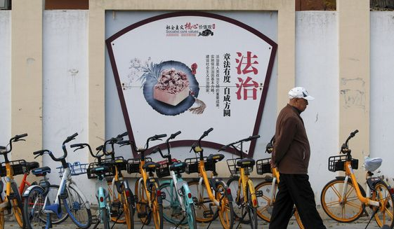 "A man walks by a propaganda board depicting China's legal system promoting the government's socialist core values near residential buildings in Beijing, Wednesday, Nov. 11, 2020. A prominent Chinese pig farmer who has publicly praised the work of lawyers who help the public amid a crackdown on legal activists by President Xi Jinping's government was subjected Monday to unspecified ""coercive measures,"" according to police, a term that usually means detention. (AP Photo/Andy Wong)"