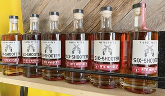 This Nov. 3, 2020 image provided by New Mexico State University shows bottles of the school's new officially licensed spirit, Pistol Pete's Six Shooter Rye Whiskey. The whiskey is bottled by Dry Point Distillers in Las Cruces, New Mexico, as part of the school's latest branding and licensing project. (Charlie Hurley, New Mexico State University, via AP)