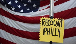 A sign hangs in front of an American flag, as a handful of supporters of President Donald Trump continue to protest outside the Pennsylvania Convention Center, in Philadelphia, Tuesday, Nov. 10, 2020. (AP Photo/Rebecca Blackwell) **FILE**