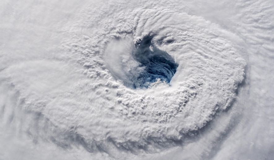 """FILE - In this Sept. 12, 2018 photo provided by NASA, Hurricane Florence churns over the Atlantic Ocean heading for the U.S. east coast as seen from the International Space Station. Astronaut Alexander Gerst, who shot the photo, tweeted: """"Ever stared down the gaping eye of a category 4 hurricane? It's chilling, even from space."""" (Alexander Gerst/ESA/NASA via AP)"""
