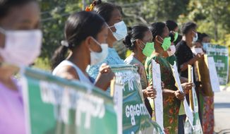 Protesters hold placards as they protest outside the Union Election Commission office, Wednesday, Nov. 11, 2020, in Naypyitaw, Myanmar. The military backed main opposition party on Wednesday said it does not recognize last Sunday's Myanmar election, citing unfairness, and rejected the results. (AP Photo/Aung Shine Oo)