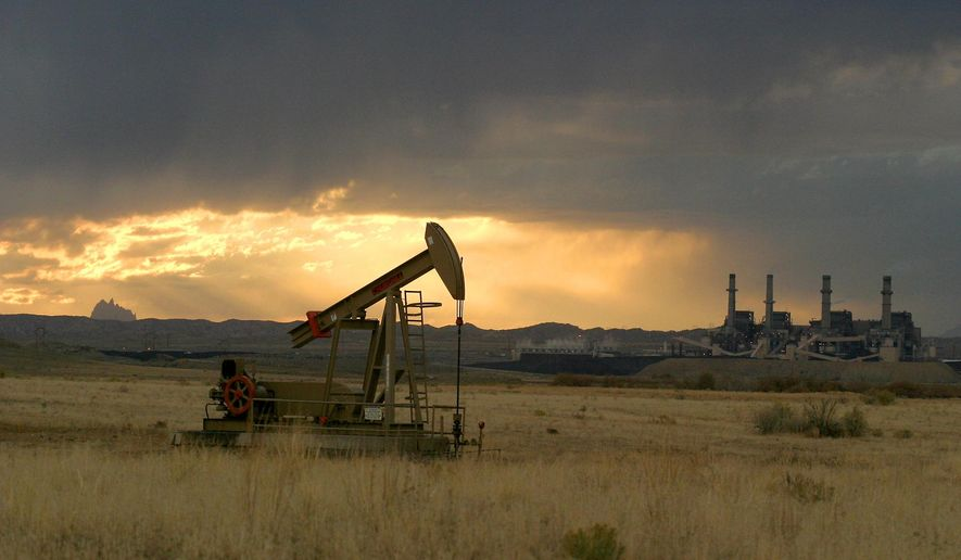 In this Nov. 8, 2004, file photo, the sun sets behind Shiprock Mountain, a pumpjack and the San Juan Generating Station near Farmington, N.M. New Mexico is on track to have another banner year as a result of oil and gas drilling and other activities on state trust lands, officials with the State Land Office said Tuesday Aug. 18, 2020. (Dave Watson/The Daily Times via AP, File)