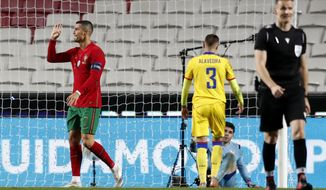 Portugal's Cristiano Ronaldo, left, reacts after scoring his teams sixth goal during the international friendly soccer match between Portugal and Andorra at the Luz stadium in Lisbon, Portugal, Wednesday, Nov. 11, 2020. (AP Photo/Armando Franca)