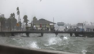 Water splashes against the seawall along Pass A Grille Way in St. Pete Beach, Fla,, on Wednesday, Nov. 11, 2020 as squalls from Tropical Storm Eta move through Pinellas County. Eta has weakened to a tropical storm just hours after regaining hurricane strength as Florida braces for a second hit from the storm. (Scott Keeler/Tampa Bay Times via AP)