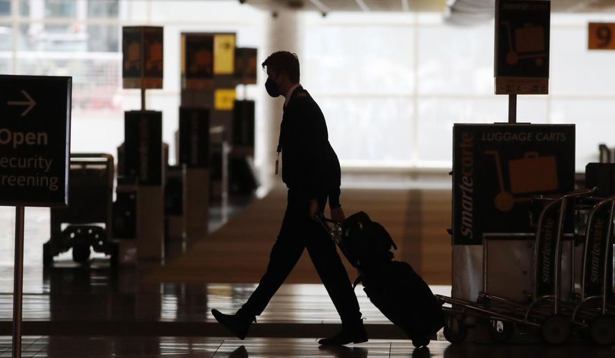 In this Thursday, April 9, 2020, file photo, a lone airline crew member pulls his bags behind him as he walks through the baggage-claim area at Denver International Airport in Denver, amid the coronavirus outbreak. (AP Photo/David Zalubowski, File)