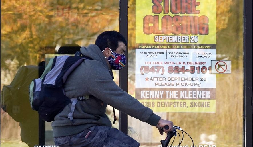 FILE - In this Friday, Nov. 6, 2020 file photo, a man wearing a face mask rides a bicycle past a closed store in Wilmette, Ill. The state set another single-day record for coronavirus infections Tuesday, Nov. 10, 2020, pushing the total number of people who have tested positive for the virus in the state since the pandemic began past 500,000. (AP Photo/Nam Y. Huh)