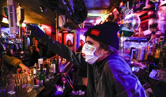 FILE - Bartender Cassandra Paris takes a farewell shot at an early closing time at 169 Bar with patrons, Monday, March 16, 2020, in New York.  Restaurants, bars and gyms will have to close at 10 p.m. across New York state in the latest effort to curb the spread of the coronavirus, Gov. Andrew Cuomo announced Wednesday, Nov. 11. Cuomo said the new restrictions, which go into effect Friday, are necessary because new coronavirus infections have been traced to those types of activities.  (AP Photo/John Minchillo)