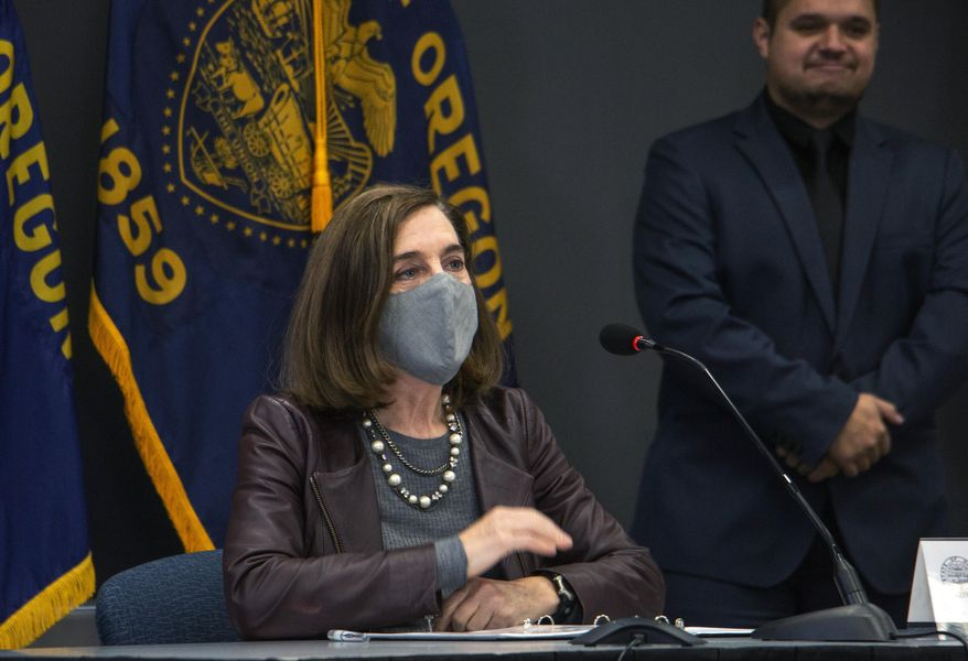 Oregon Gov. Kate Brown attends a news conference Tuesday, Nov. 10, 2020, in Portland, Ore. Brown and Oregon health officials warned Tuesday of the capacity challenges facing hospitals as COVID-19 case counts continue to spike in the state. (Cathy Cheney/Pool Photo via AP)