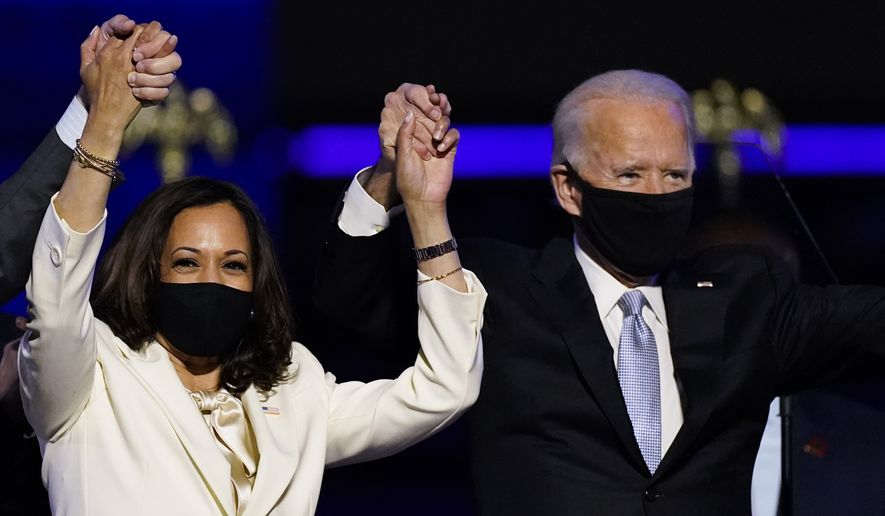 FILE - In this Nov. 7, 2020, file photo Vice President-elect Kamala Harris holds hands with President-elect Joe Biden and her husband Doug Emhoff as they celebrate in Wilmington, Del. Black policy leaders will play a pivotal role in President-elect Joe Bidens transition team, marking one of the most diverse presidential agency review teams in history. (AP Photo/Andrew Harnik, File)
