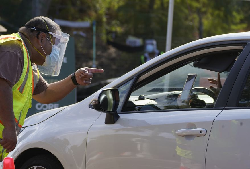 Drivers with an appointment wait in line to get a free COVID-19 self-test at Dodger Stadium, Thursday, Nov. 12, 2020 in Los Angeles. California has become the second state to record 1 million confirmed coronavirus infections. (AP Photo/Damian Dovarganes)