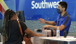 FILE - In this June 24, 2020 file photo, Southwest Airlines employee Oscar Gonzalez, right, assists a passenger at the ticket counter at Love Field in Dallas. Southwest Airlines cautioned Thursday, Nov. 12, 2020 that the tenuous recovery in air travel could be fading as coronavirus cases spike across the United States. The nation's fourth-biggest airline said after a modest rise in leisure-travel bookings from August through October, it now sees a slowdown in improving revenue trends for November and December. (AP Photo/Tony Gutierrez, File)