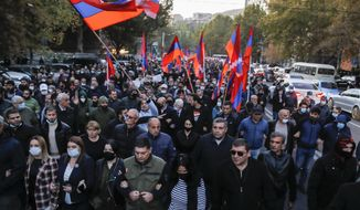 Protesters with Armenian flags walk along a street during a protest against an agreement to halt fighting over the Nagorno-Karabakh region, in Yerevan, Armenia, Thursday, Nov. 12, 2020. Thousands of people flooded the streets of Yerevan once again on Wednesday, protesting an agreement between Armenia and Azerbaijan to halt the fighting over Nagorno-Karabakh, which calls for deployment of nearly 2,000 Russian peacekeepers and territorial concessions. Protesters clashed with police, and scores have been detained. (AP Photo/Dmitri Lovetsky)
