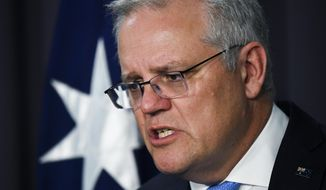 Australian Prime Minister Scott Morrison speaks to the media during a press conference at Parliament House in Canberra, Thursday, Nov. 12, 2020. Morrison announced a new investigative agency to build criminal cases against Australian special forces suspected of committing war crimes in Afghanistan. (Lukas Coch/AAP Image via AP)