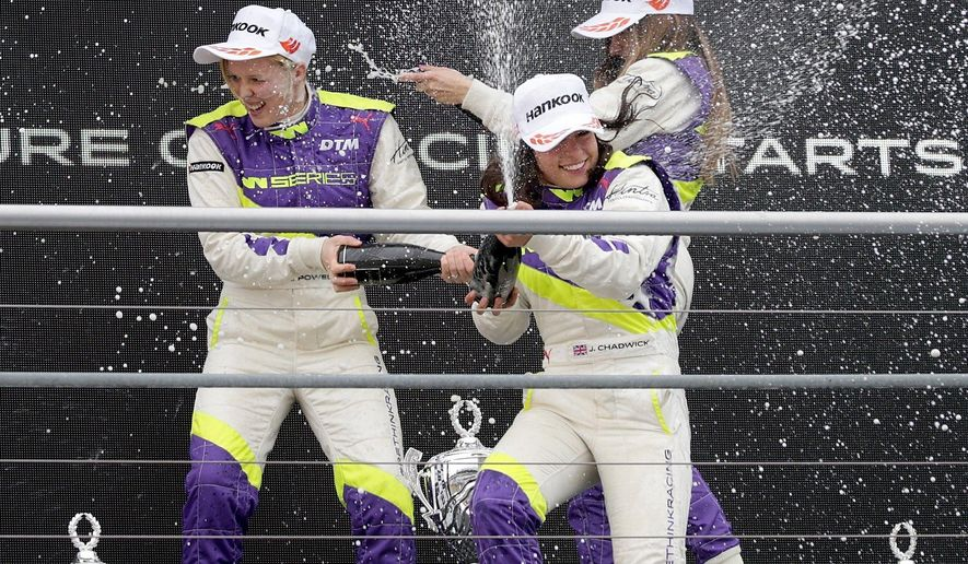 """FILE - In this Saturday, May 4, 2018 file photo, Jamie Chadwick, center, celebrates with Alice Powell, left, and Marta Garcia after she wins the inaugural car race of the new all-female W Series at Hockenheim, Germany. Formula One world champion Lewis Hamilton praised the decision to host eight races of the all-female W Series alongside F1 races next season, calling it an important step in the push for greater diversity and inclusion in motorsport. """"When we talk about diversity people often think that we're talking about having more people of color. It's not just that,"""" Hamilton said Thursday, Nov. 12, 2020 at the Turkish F1 GP in Istanbul. """"It is having more women involved. At the moment it is a male dominated sport and that does need to change."""" (Hasan Bratic/dpa via AP, file)"""