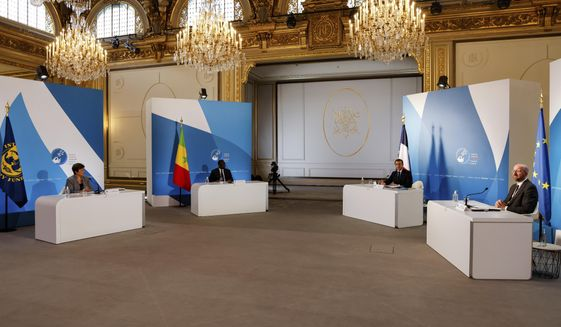 French President Emmanuel Macron, second right, European Council President Charles Michel, right, Senegal's President Macky Sall, second left, and International Monetary Fund Managing Director Kristalina Georgieva attend The Paris Peace Forum at The Elysee Palace in Paris, Thursday, Nov. 12, 2020. (Ludovic Marin, Pool via AP)