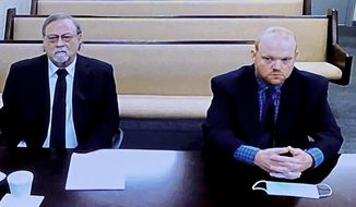In this image made from video, from left, father and son, Gregory and Travis McMichael, accused in the shooting death of Ahmaud Arbery in Georgia on Feb. 2020, listen via closed circuit tv in the Glynn County Detention center in Brunswick, Ga., on Thursday, Nov. 12, as lawyers argue for bond to be set at the Glynn County courthouse. The McMichaels chased and fatally shot Ahmaud Arbery, a 25-year-old Black man, after they spotted him running in their neighborhood just outside the port city of Brunswick.(AP Photo/Lewis Levine)