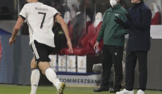 Germany's head coach Joachim Low, right, watches the friendly soccer match between Germany and Czech Republic in Leipzig, Germany, Wednesday, Nov. 11, 2020. (AP Photo/Michael Sohn)