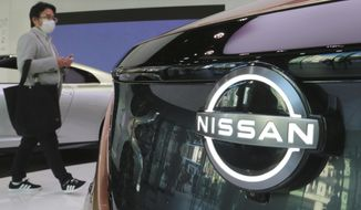 A visitor walks past a car at Nissan Motor Co.'s showroom in Tokyo, Wednesday, Nov. 11, 2020. Nissan posted a loss of 44.4 billion yen ($421 million) for the fiscal second quarter, as the coronavirus pandemic slammed profitability, and the Japanese automaker fought to restore brand image tarnished by the scandal of its former star executive Carlos Ghosn, reported Thursday, Nov. 12, 2020. (AP Photo/Koji Sasahara)