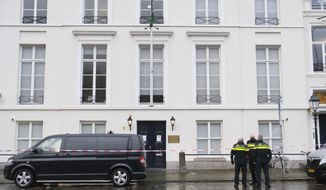 Dutch police are seen outside Saudi Arabia's embassy in The Hague, Netherlands, Thursday, Nov. 12, 2020, after several shot were fired at the building early in the morning. Nobody was injured and police were investigating. (AP Photo/Mike Corder)