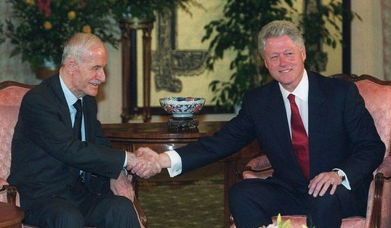 In this March 26, 2000, file photo, U.S. President Bill Clinton, right, shakes hands with Syrian President Hafez Assad, at the opening of their meeting, in Geneva, Switzerland. On Nov. 13, 1970, Assad a young career air force officer launched a bloodless coup. Fifty years later, Hafez Assad's family still rules Syria. The country is in ruins from a decade of civil war that killed around a half million people, displaced half the population and virtually wiped out the economy. But Hafez's son, Bashar Assad, has an unquestioned grip on what remains. (AP Photo/Laurent Gillieron, File)