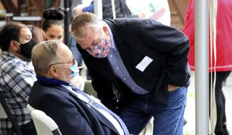 In this Aug. 26, 2020, photo, a masked U.S. Sen. Dan Sullivan leans down to speak to U.S. Rep. Don Young, also masked, before a ceremony in Anchorage, Alaska, celebrating the opening of a Lady Justice Task Force cold case office which will specialize in cases involving missing or murdered Indigenous women. Young announced Thursday, Nov. 12, 2020, on Twitter that he has tested positive for COVID-19. (AP Photo/Mark Thiessen)
