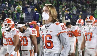 In this Saturday, Nov. 7, 2020 file photo, Clemson quarterback Trevor Lawrence (16) leaves the field with his teammates after Clemson lost to Notre Dame 47-40 in two overtimes during an NCAA college football game in South Bend, Ind. As virus disruptions mount and the Dec. 19 end of college football's regular season draws closer, the possibility grows that conference championships, major awards and even College Football Playoff participants will be determined by COVID-19. (Matt Cashore/Pool Photo via AP, File)  **FILE**
