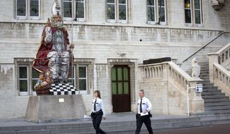 FILE - In this Thursday, Nov. 13, 2014 file photo, two police officers walk by a giant statue of Saint Nicolas in front of the town hall of Sint-Niklaas, Belgium. To ensure the merriment of millions of Belgian kids this year, the government is offering a special exemption from the stringent coronavirus measures to beloved Saint Nicholas, who always delivers bountiful presents on the morning of Dec. 6. (AP Photo/Virginia Mayo, File)