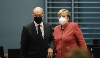 German Chancellor Angela Merkel, right, and German Finance Minister Olaf Scholz arrive at the weekly cabinet meeting of the German government at the chancellery in Berlin, Germany, Wednesday, Nov. 11, 2020. (AP Photo/Markus Schreiber, pool)