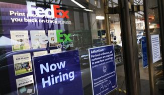 "A sign in the window of a FedEx office reads, ""Now Hiring,"" Monday, Oct. 26, 2020 in New York.  Carriers like FedEx and UPS are ramping up their holiday hiring while asking store clients to move their shipping volume on lighter days in their network.  (AP Photo/Mark Lennihan)"