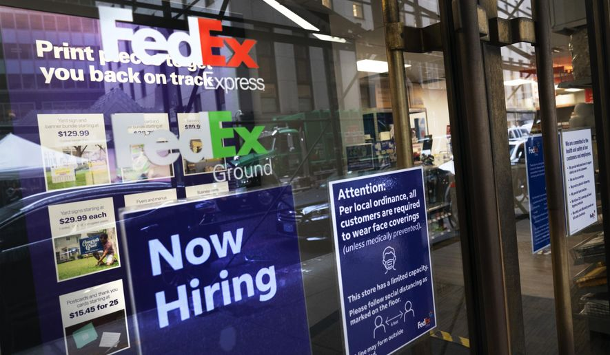 """A sign in the window of a FedEx office reads, """"Now Hiring,"""" Monday, Oct. 26, 2020 in New York.  Carriers like FedEx and UPS are ramping up their holiday hiring while asking store clients to move their shipping volume on lighter days in their network.  (AP Photo/Mark Lennihan)"""