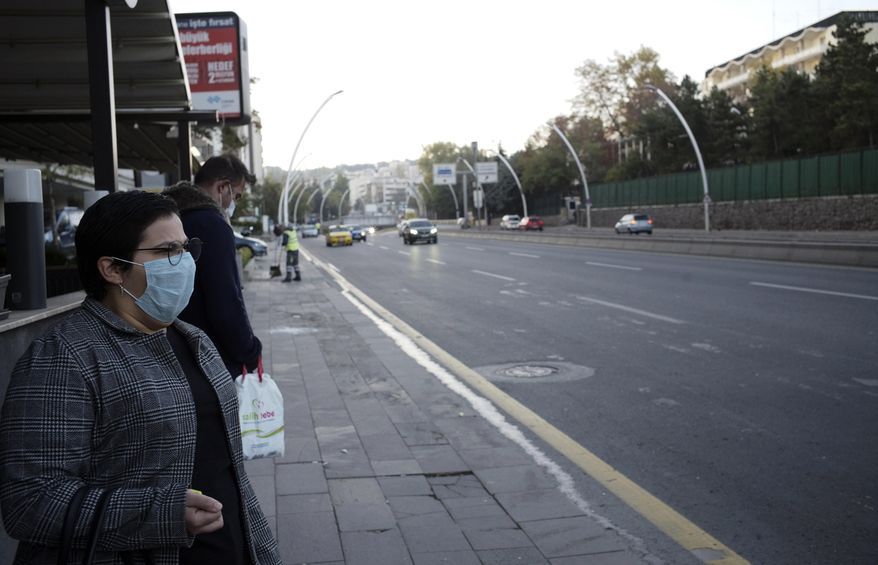 People wearing masks to help protect against the spread of coronavirus, wait at a bus station, in Ankara, Turkey, Wednesday, Nov. 11, 2020. Turkey's government had urged the residents of big cities to limit their mobility and called on employers to offer workers flexible or staggered working hours and the possibility of working from homes.(AP Photo/Burhan Ozbilici)