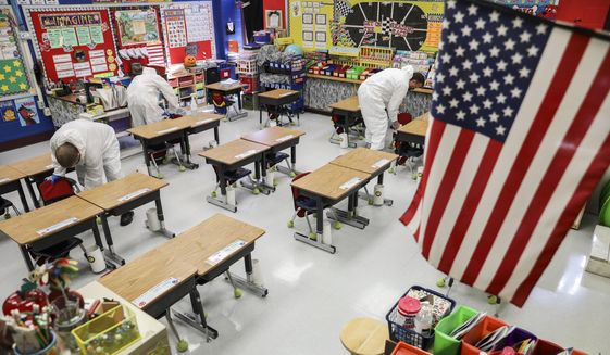 In this Nov. 5, 2020, file photo, custodial workers clean a classroom at an elementary school in Missouri. On Dec. 3, 2020, the Montgomery County [Maryland] Board of Education postponed until Dec. 15 a vote on a plan to reopen schools. (Colter Peterson/St. Louis Post-Dispatch via AP, File)  **FILE**