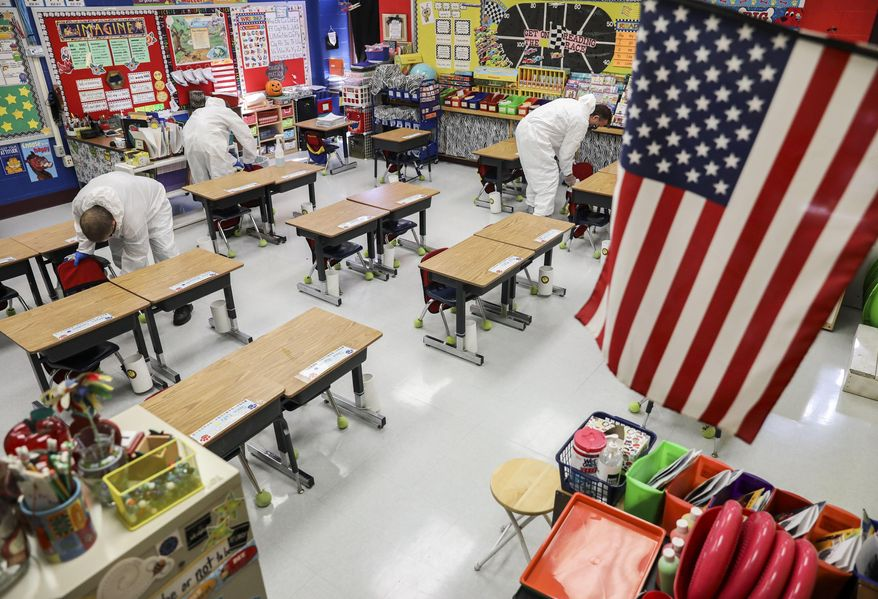 In this Nov. 5, 2020, file photo, custodial workers clean a classroom at an elementary school in Missouri. On Feb. 9, 2021, the Montgomery County [Md.] board of education voted to bring students back into classrooms starting March 1. (Colter Peterson/St. Louis Post-Dispatch via AP, File)  **FILE**