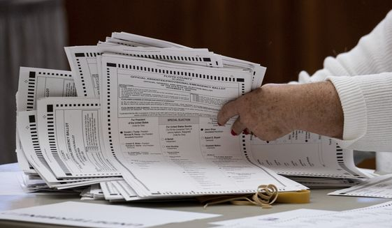 Officials sort ballots during an audit at the Floyd County administration building in Rome, Ga. on Friday morning, Nov. 13, 2020. Election officials in Georgia's 159 counties are undertaking a hand tally of the presidential race that stems from an audit required by state law.  (AP Photo/Ben Gray)