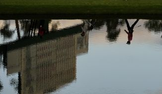 Dylan Frittelli, of South Africa, is reflected in the water has he walks along the 16th fairway during the first round of the Masters golf tournament Thursday, Nov. 12, 2020, in Augusta, Ga. (AP Photo/Matt Slocum)