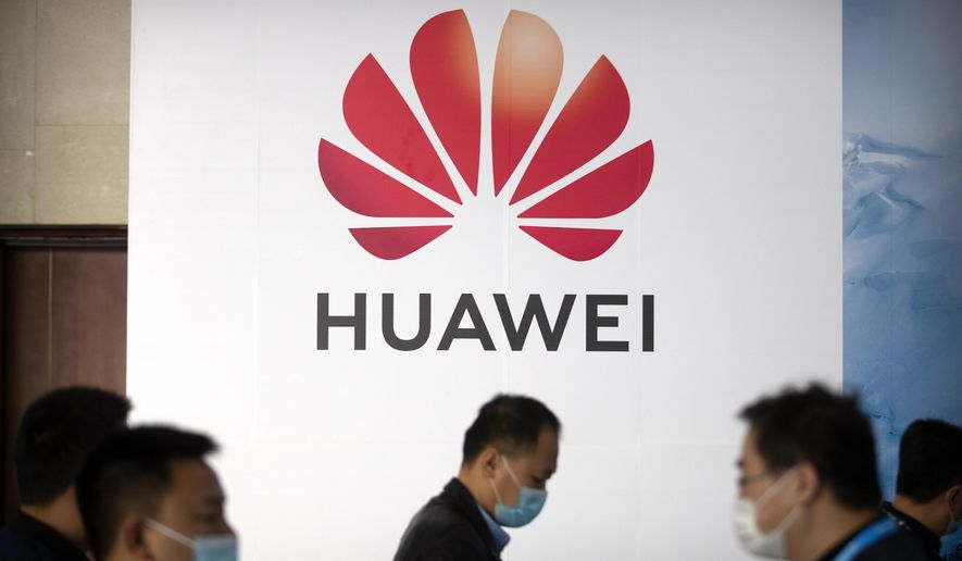People walk past a billboard advertising Chinese tech company Huawei at the PT Expo in Beijing on Oct. 14, 2020. U.S. President Donald Trump has stepped up a conflict with China over security and technology by issuing an order barring Americans from investing in companies that U.S. officials say are owned or controlled by the Chinese military. (AP Photo/Mark Schiefelbein)