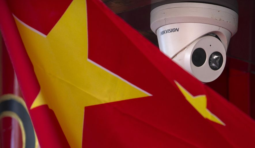 A Chinese flag hangs near a Hikvision security camera outside of a shop in Beijing on Oct. 8, 2019. U.S. President Donald Trump has stepped up a conflict with China over security and technology by issuing an order barring Americans from investing in companies that U.S. officials say are owned or controlled by the Chinese military. (AP Photo/Mark Schiefelbein)